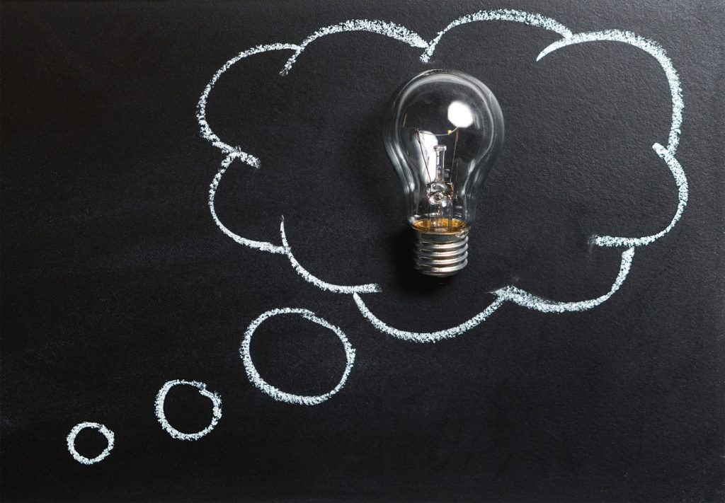 Inside a white chalk outline of a thought bubble drawn on a chalkboard, lies a real light bulb.