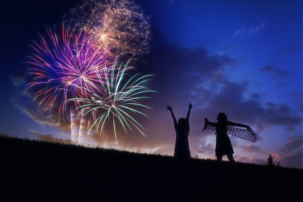 Silhouetted against a blue sky with darker blue clouds, 3 fireworks in purple, yellow-orange, and green, is a black hill and 2 women celebrating.