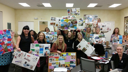 A group of people holding up their vision boards after a successful vision coaching session with Terri L. Moore.