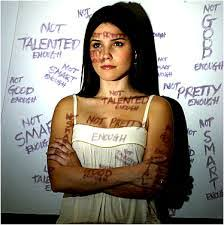 An image a of woman standing in front a whiteboard with negative words projected over her.